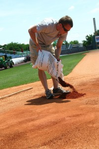 Trotter repairing the home plate area in the batter's box, filling in holes with a clay soil that will be compacted into a study surface for batters. PHOTO BY MATTHEW W MAXEY