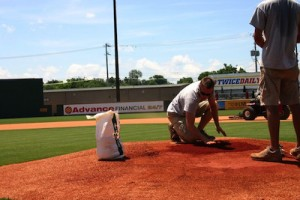 Trotter showing one of his two interns the proper way to smooth out the replacement clay on the pitcher's mound before using a tamping tool to make it as compact as possible. / PHOTO BY MATTHEW W MAXEY