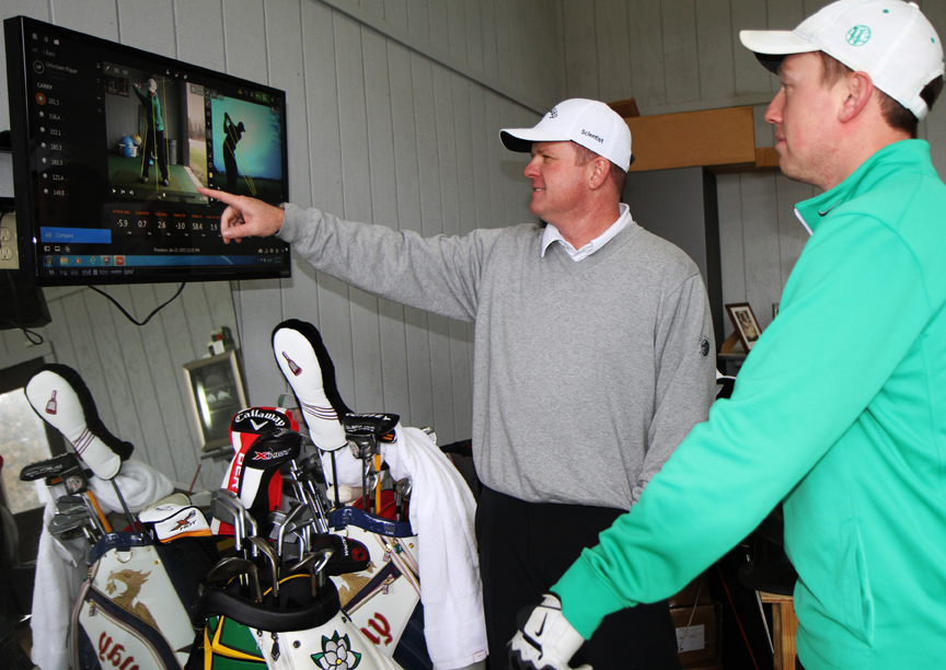 Inside the Westhaven Golf Academy, Herring demonstrates to Director of Player Development Matt Walter the TracMan technology used to analyze a student's swing and ball speed. PHOTO BY MATTHEW MAXEY